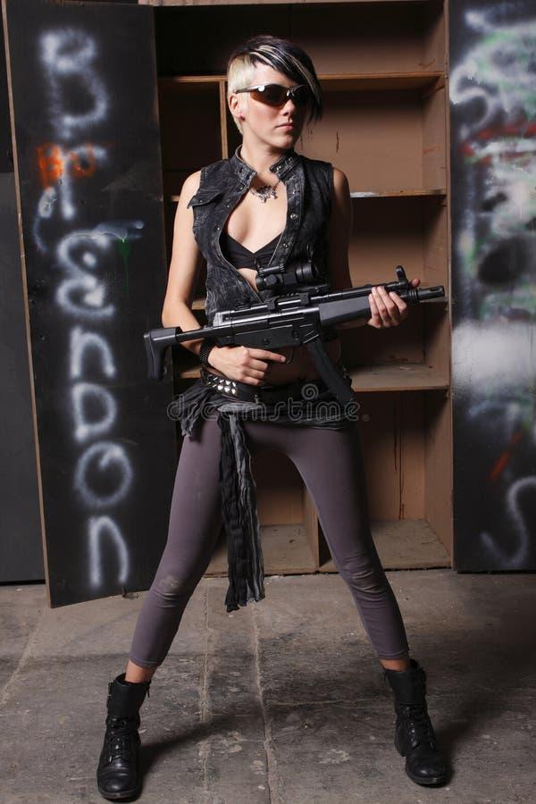 Giovane donna con il fucile di assalto immagini stock