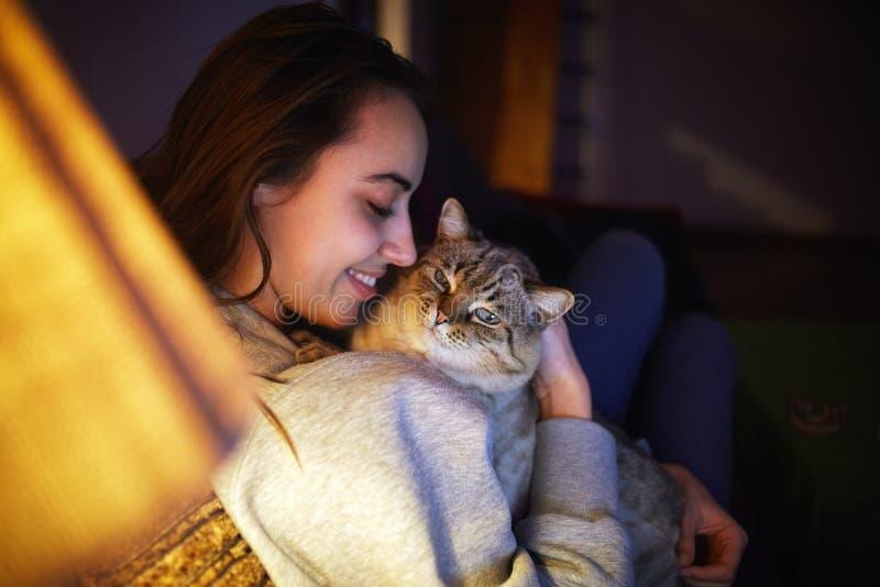 Giovane donna con il gatto alla sera immagine stock