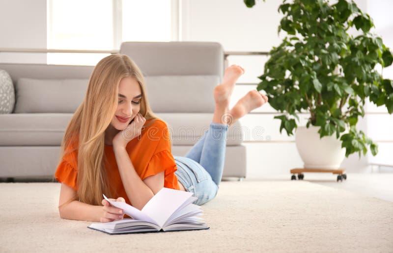 Giovane donna con il libro che si trova sul pavimento immagine stock libera da diritti