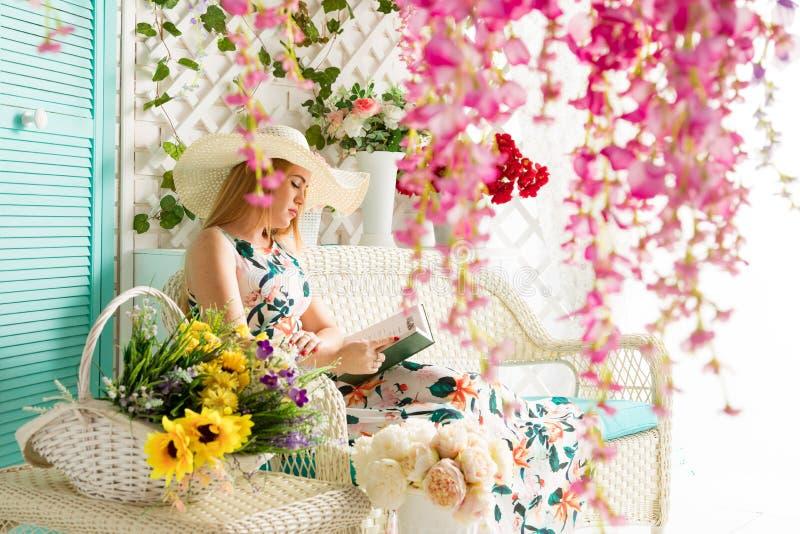 Giovane donna con il libro nel terrazzo di estate immagine stock