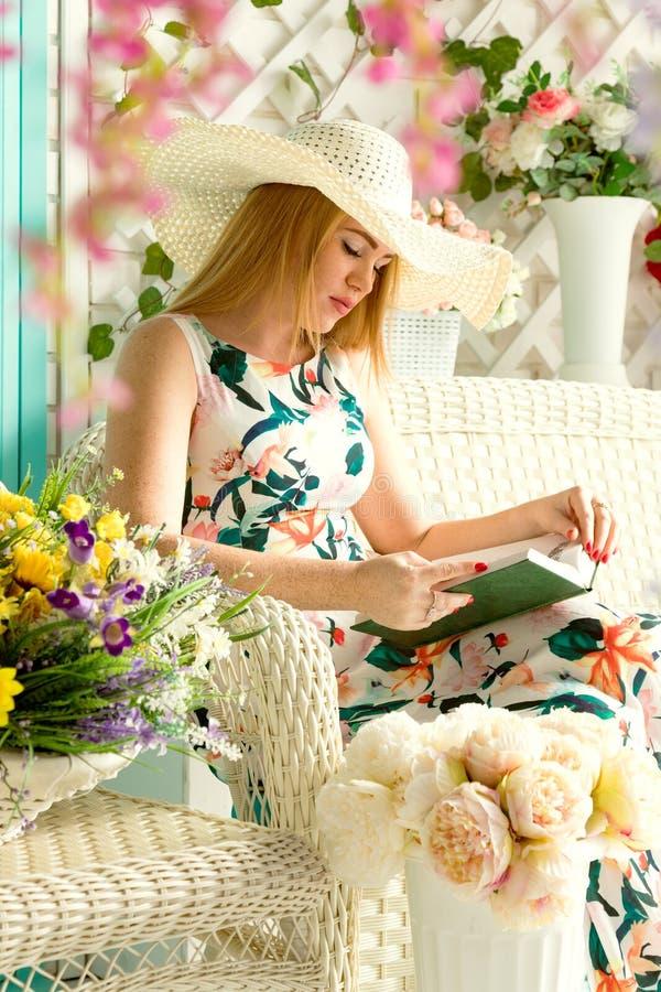 Giovane donna con il libro nel terrazzo di estate immagini stock libere da diritti