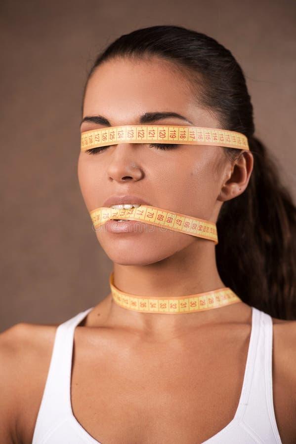 Giovane donna con il metro che chiude la sua bocca fotografia stock libera da diritti