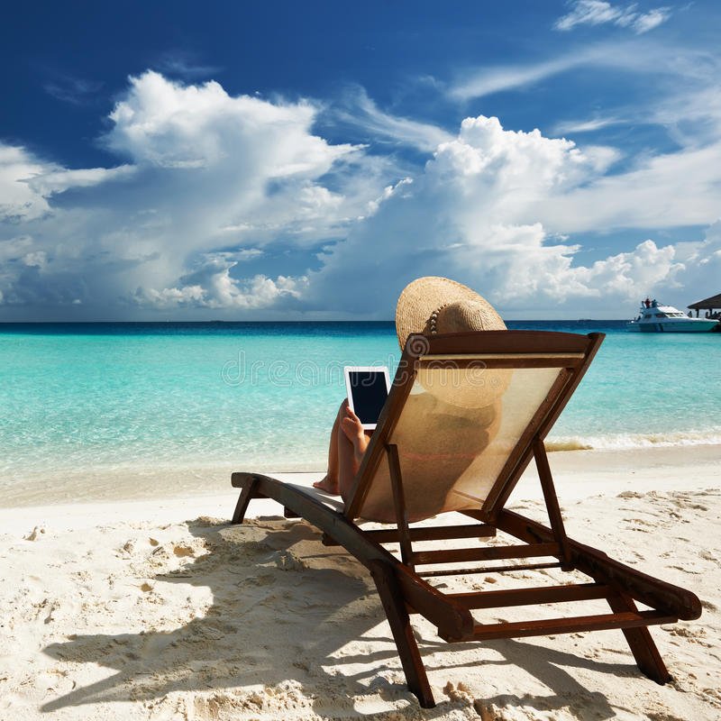 Giovane donna con il pc della compressa alla spiaggia - Alla colorazione della spiaggia ...