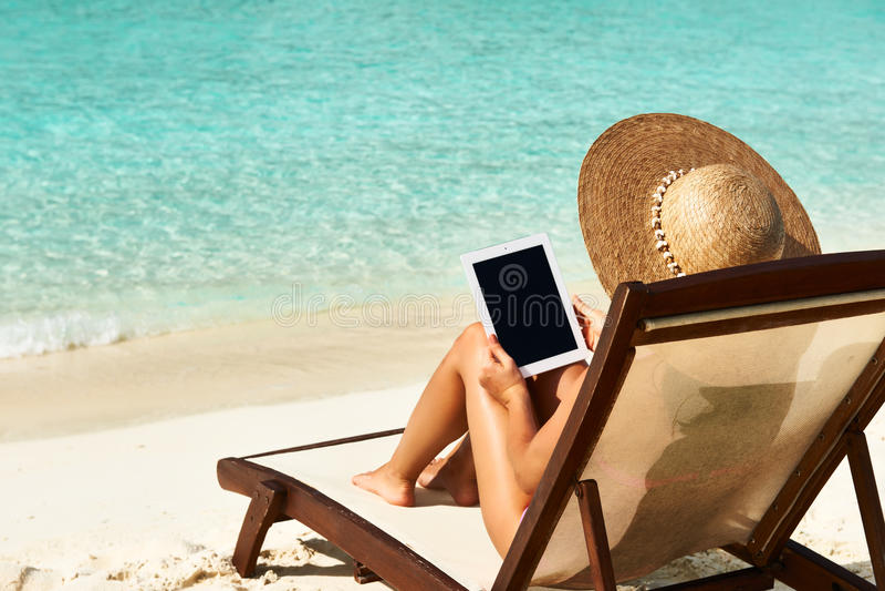 Giovane donna con il pc della compressa alla spiaggia fotografia stock