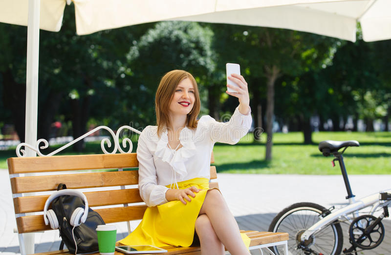 Giovane donna con il pc della compressa nel parco immagine stock