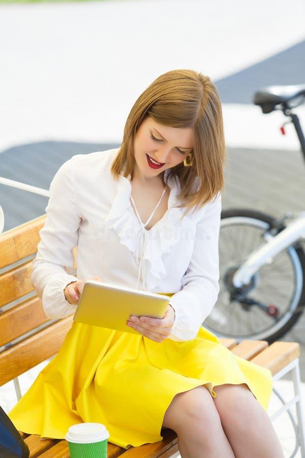 Giovane donna con il pc della compressa nel parco immagine stock libera da diritti
