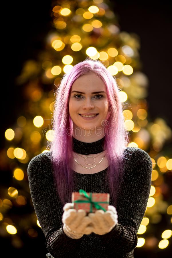Giovane donna con il regalo, l'albero di Natale ed il fondo decorativo del bokeh di illuminazione Abete rosso con le decorazioni immagini stock libere da diritti
