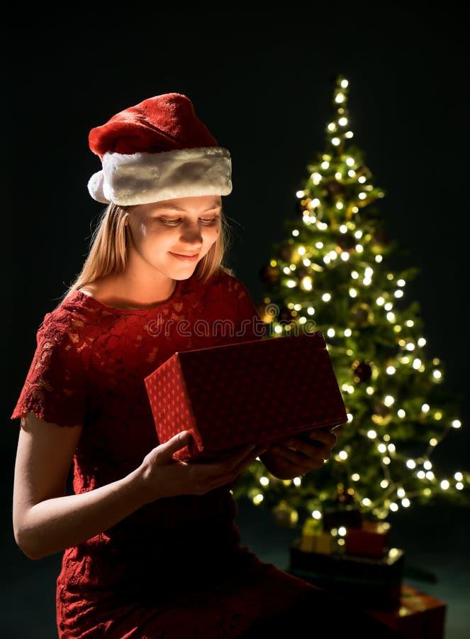Giovane donna con il regalo, l'albero di Natale ed il fondo decorativo del bokeh di illuminazione Elf ed abete rosso con le decor fotografia stock libera da diritti