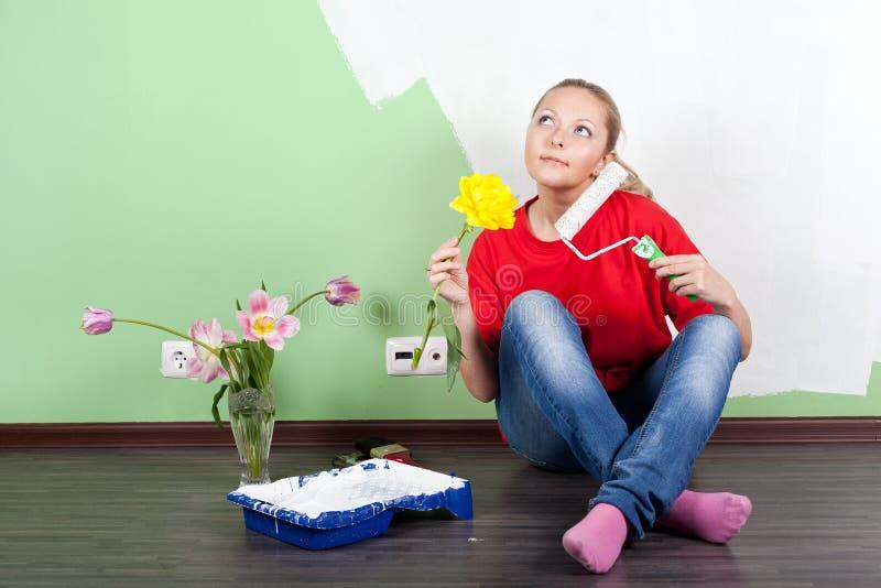 Giovane donna con il rullo di vernice e del fiore in mani fotografie stock