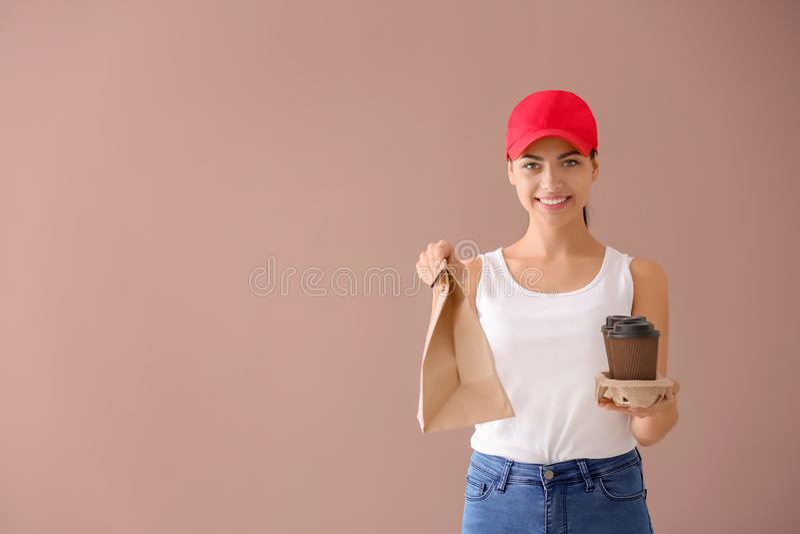 Giovane donna con il sacco di carta e tazze di caffè sul fondo di colore Servizio di distribuzione dell'alimento fotografia stock