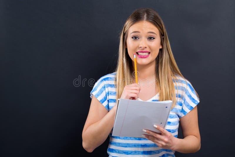 Giovane donna con il taccuino e la matita immagine stock