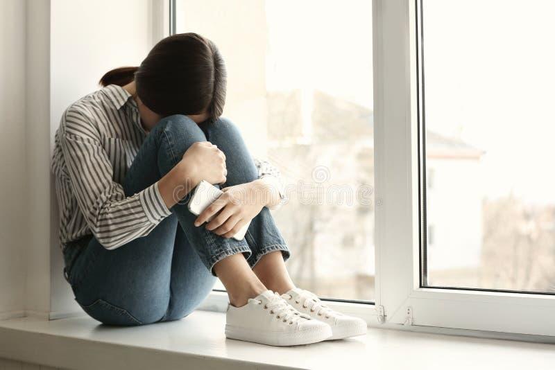 Giovane donna con il telefono cellulare che grida sul davanzale della finestra Concetto di solitudine immagini stock