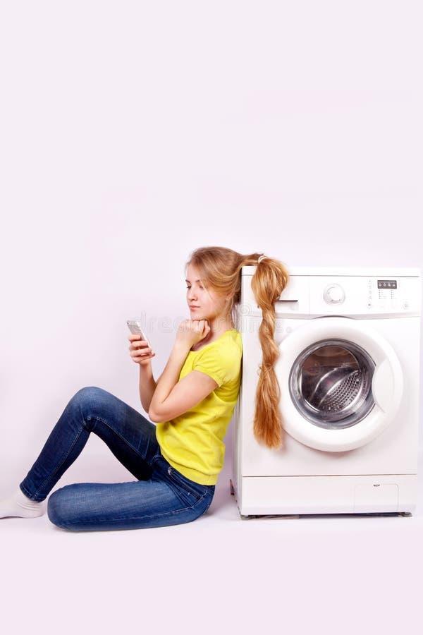 Giovane donna con il telefono cellulare e la lavatrice isolati apparecchi Elettronica immagini stock