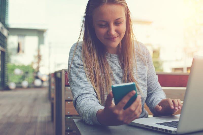 Giovane donna con il telefono cellulare ed il computer portatile che si siedono in caffè della via, navigando web e l'alimentazio fotografia stock libera da diritti
