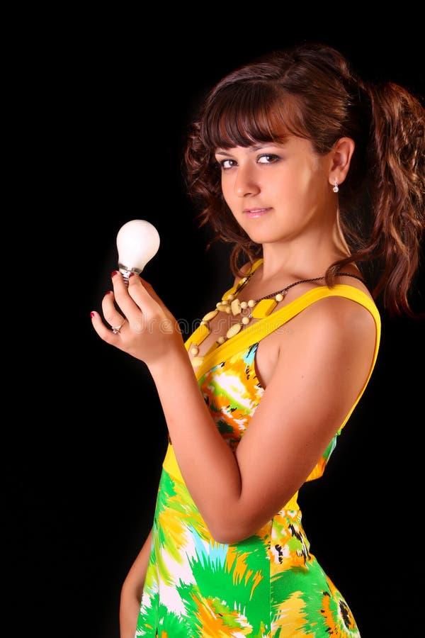 Giovane donna con il tubo della lampada sul nero immagini stock