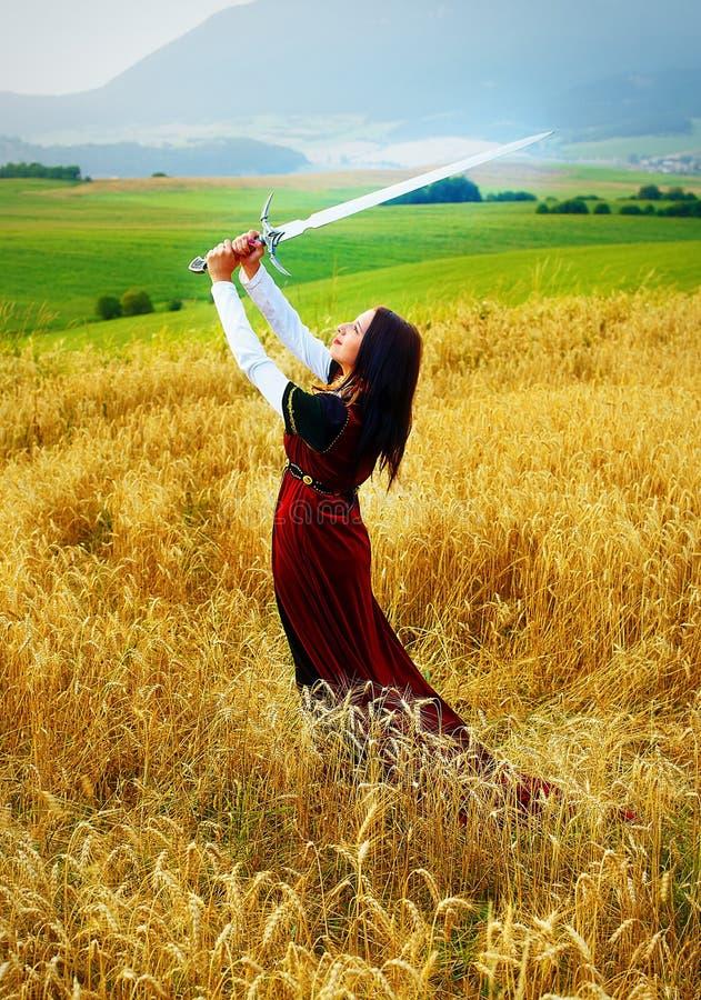 Giovane donna con il vestito ornamentale e la spada a disposizione che stanno su un giacimento di grano con il tramonto Sfondo na fotografie stock libere da diritti