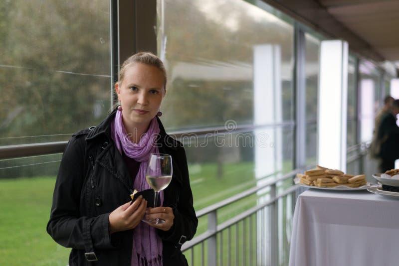 Giovane donna con il vetro di vino al partito immagini stock