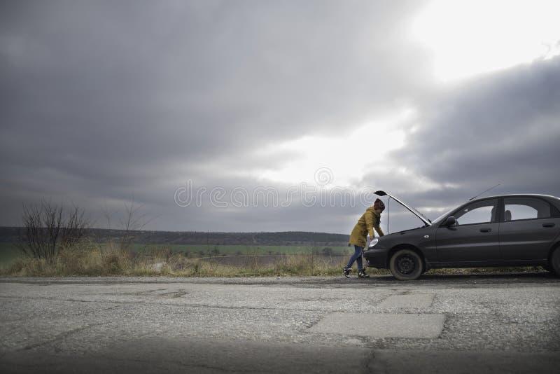 Giovane donna con l'automobile rotta fotografia stock libera da diritti