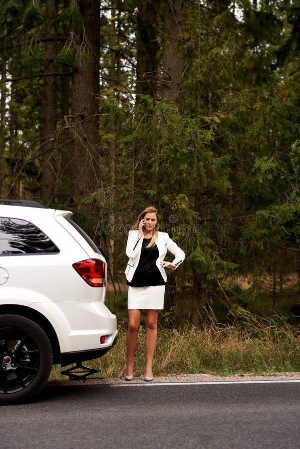 Giovane donna con l'automobile rotta che richiede l'aiuto fotografia stock