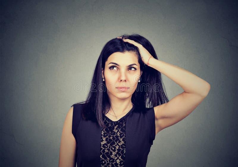 Giovane donna con l'espressione preoccupata dubbiosa del fronte fotografia stock libera da diritti