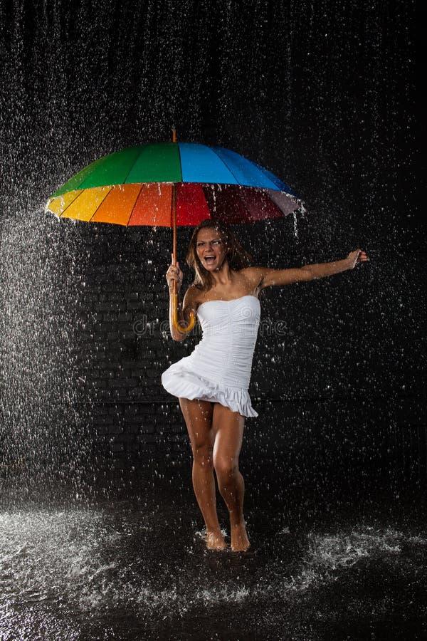 Giovane donna con l'ombrello multi-coloured. immagine stock