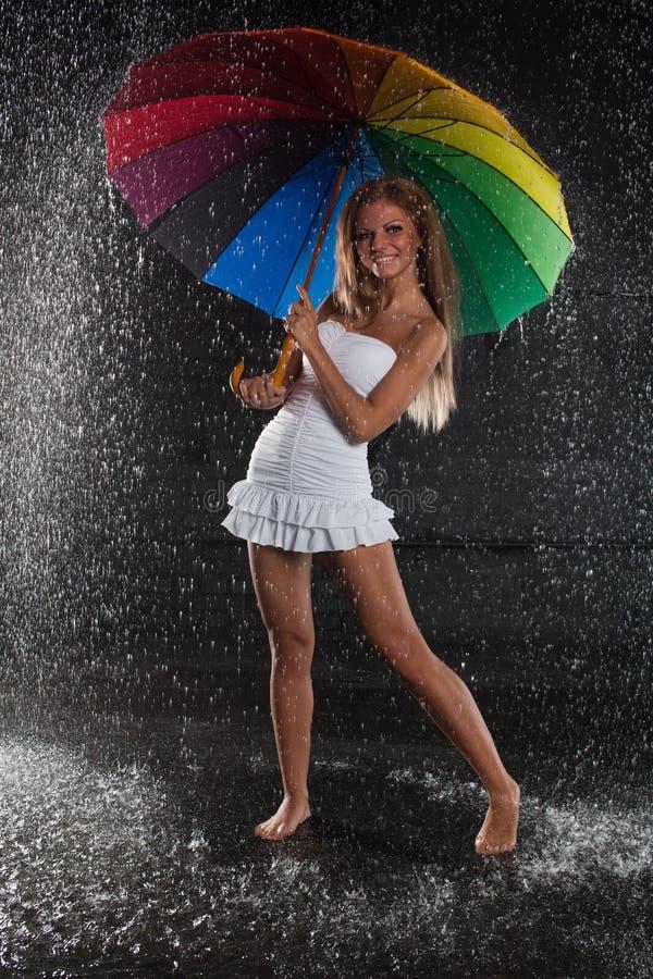 Giovane donna con l'ombrello multi-coloured. immagini stock