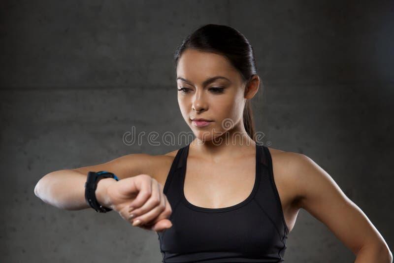 Giovane donna con l'orologio di cuore-rate in palestra fotografia stock