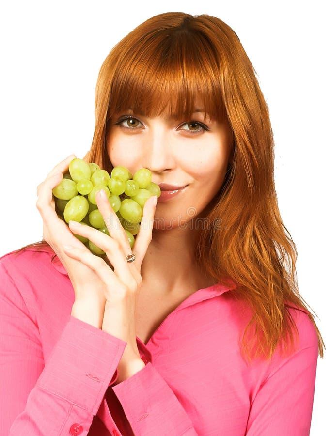 Giovane donna con l'uva verde immagine stock