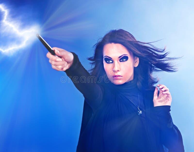 Giovane donna con la bacchetta magica. immagini stock