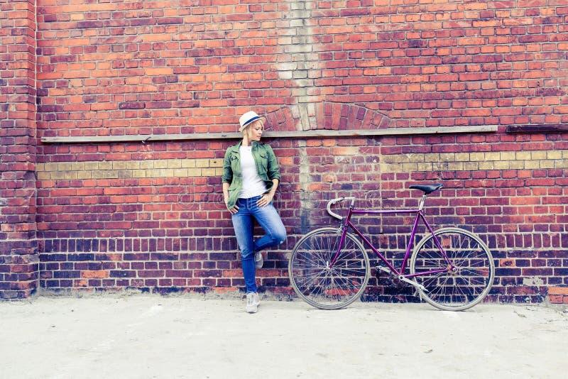 Giovane donna con la bici d'annata della strada in città fotografia stock