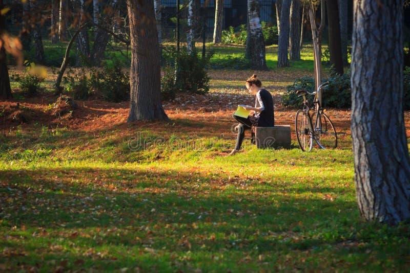 Giovane donna con la bicicletta, leggente nel parco fotografia stock