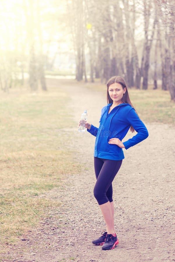 Giovane donna con la bottiglia di acqua a disposizione prima del funzionamento Un modo di vivere sano yoga di forma fisica di spo fotografia stock