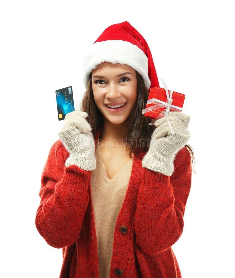 Giovane donna con la carta di credito e regalo di Natale su fondo bianco fotografie stock