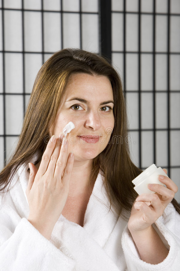 Giovane donna con la crema di fronte immagine stock libera da diritti