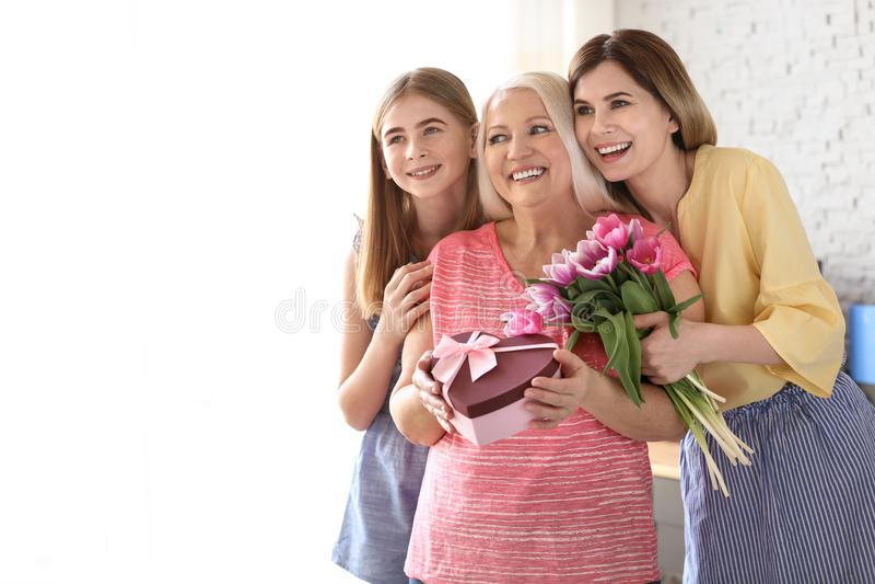 Giovane donna con la figlia che si congratula membro della famiglia maturo a casa immagini stock