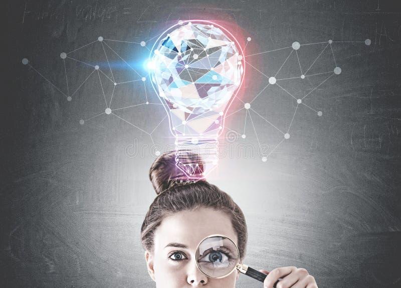 Giovane donna con la lente d'ingrandimento, idea fotografia stock