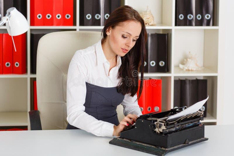 Giovane donna con la macchina da scrivere. fotografia stock libera da diritti