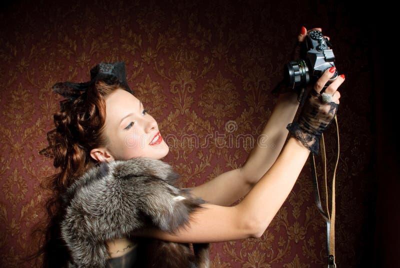 Giovane donna con la macchina fotografica immagine stock