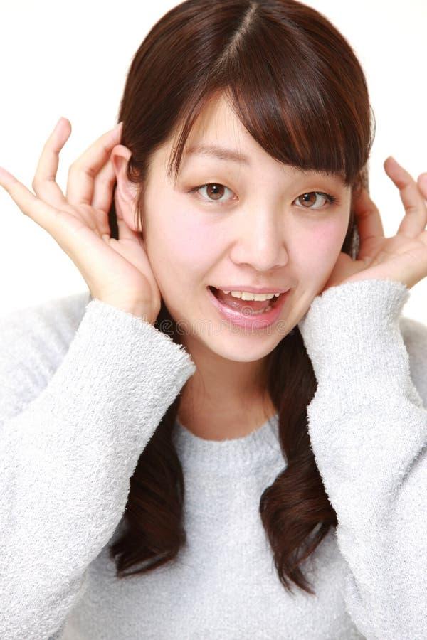 Giovane donna con la mano dietro l'orecchio che ascolta molto attentamente fotografia stock