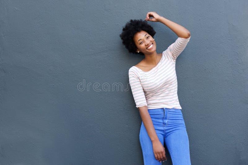 Giovane donna con la mano nel sorridere dei capelli di afro immagini stock libere da diritti