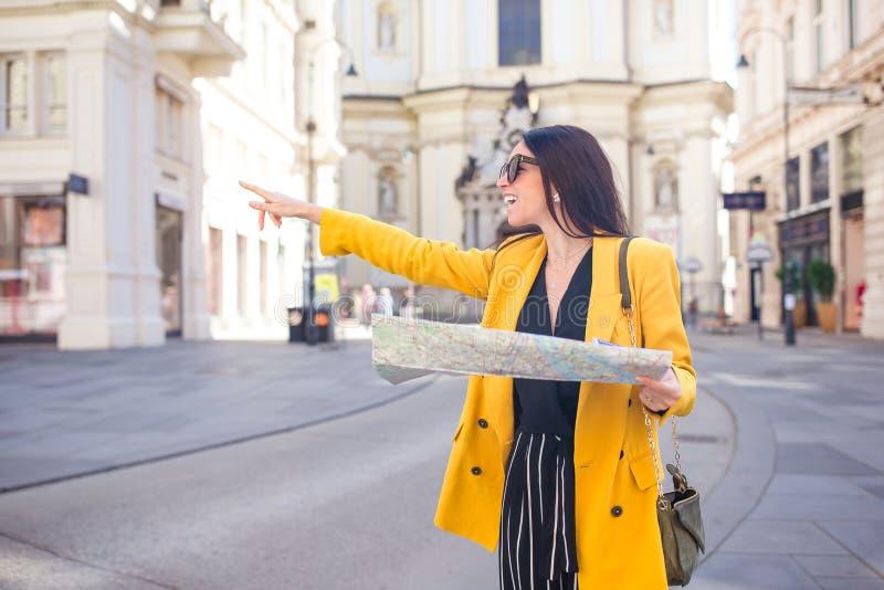 Giovane donna con la mappa della città in città Ragazza turistica di viaggio con la mappa a Vienna all'aperto durante le feste in immagini stock libere da diritti