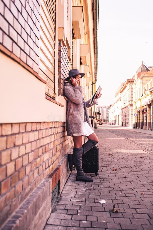 Giovane donna con la mappa e valigia in via della città fotografie stock