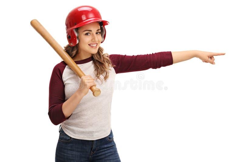 Giovane donna con la mazza da baseball e casco che indicano destra fotografie stock