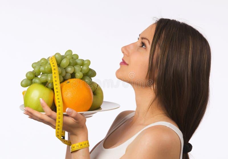 Giovane donna con la misura di nastro e della frutta fresca fotografia stock libera da diritti
