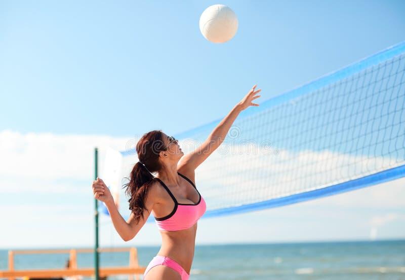 Giovane donna con la palla che gioca pallavolo sulla spiaggia fotografie stock libere da diritti