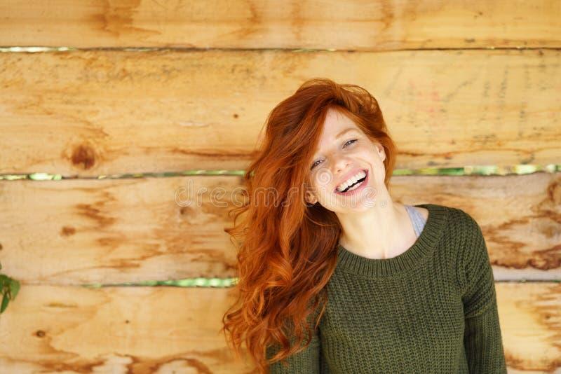 Giovane donna con la risata rossa lunga dei capelli fotografia stock libera da diritti