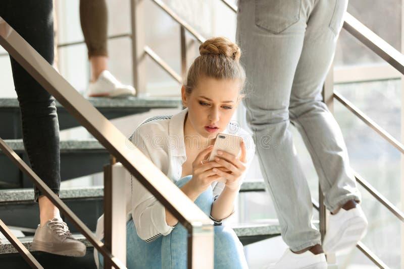 Giovane donna con la seduta dello smartphone Da solo fra la gente immagini stock libere da diritti