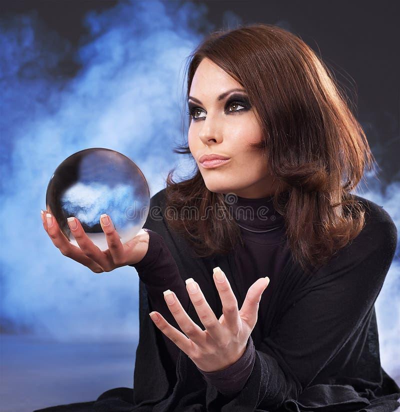 Giovane donna con la sfera di cristallo. fotografia stock libera da diritti