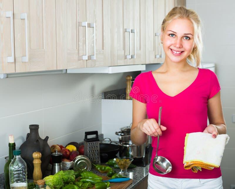 Giovane donna con la siviera alla cucina immagini stock
