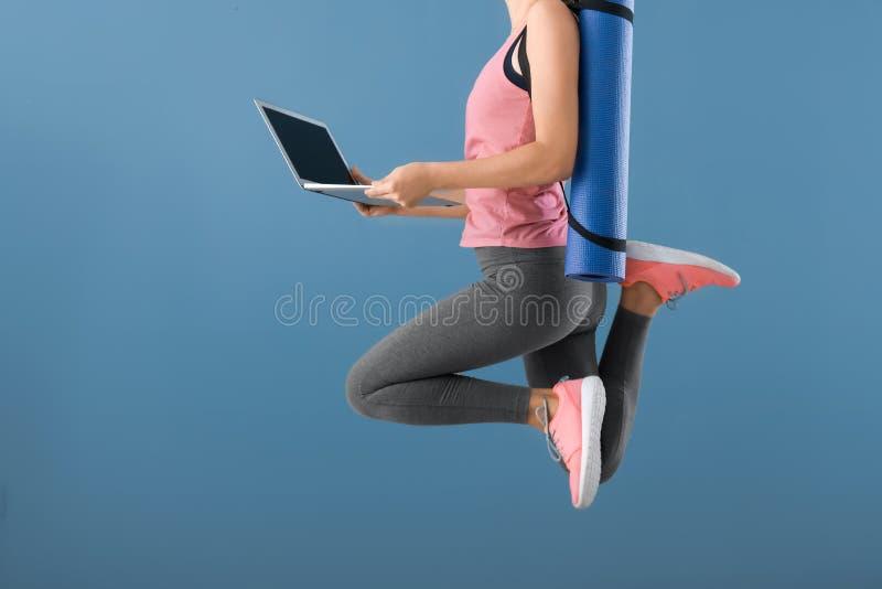 Giovane donna con la stuoia ed il computer portatile di yoga che saltano sul fondo di colore Concetto di equilibrio fra riposo e  fotografie stock